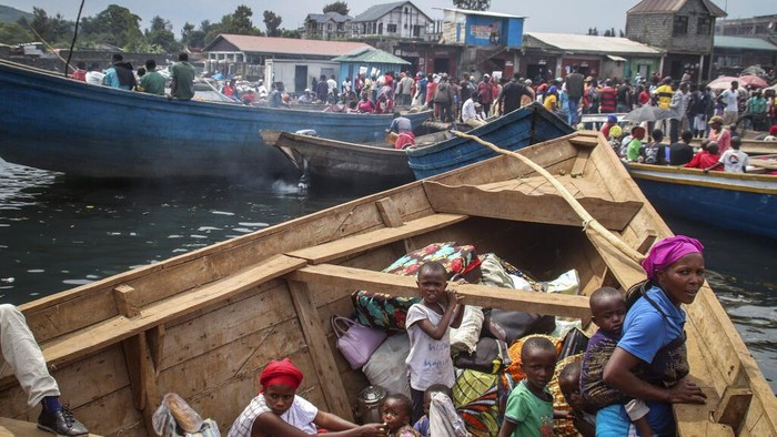Residents board boats to flee across Lake Kivu in the direction of South Kivu province, at the port of Kituku in Goma, in eastern Congo Friday, May 28, 2021. Tens of thousands of people are fleeing the city of Goma in eastern Congo fearing another volcanic eruption by Mount Nyiragongo, which spewed lava near the city last week. (AP Photo/Justin Kabumba)