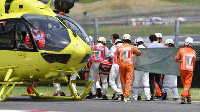 Medical officers clear the track as they evacuate Swiss Moto3 rider Jason Dupasquier in an helicopter after a crash during a qualifying session ahead the Italian Moto GP Grand Prix at the Mugello race track in Scarperia e San Piero on May 29, 2021. - Swiss Moto3 rider Jason Dupasquier was being taken to hospital after a three-bike crash that halted qualifying for the Italian motorcycling Grand Prix at Mugello on May 29, 2021. Organisers said the stricken teenager was being taken to hospital in Florence to undergo tests. Japanese rider Ayumu Sasaki and Spaniard Jeremy Alcoba were the others involved in the accident which delayed the MotoGP fourth practice with organisers reporting both were fine. (Photo by Tiziana FABI / AFP)