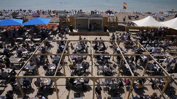 Seorang penyanyi tampil saat orang makan dan minum di meja yang disediakan di Pantai Brighton.