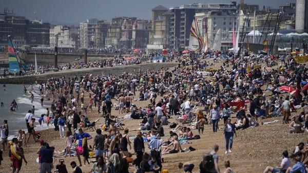 Orang-orang berkumpul di Pantai Brighton, Selatan Inggris, Minggu (30/5/2021) waktu setempat.