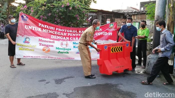 Pembukaan isolasi wilayah terkait kasus virus Corona klaster kampung Jokowi, Solo, Senin (31/5/2021).