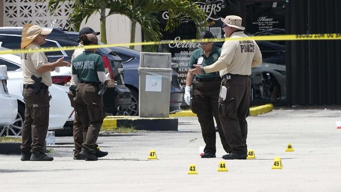 People wait for information outside the scene of a shooting at a banquet hall near Hialeah, Fla., Sunday, May 30, 2021. Two people died and an estimated 20 to 25 people were injured in a shooting outside a banquet hall in South Florida, police said. The gunfire erupted early Sunday at the El Mula Banquet Hall in northwest Miami-Dade County, near Hialeah, police told news outlets. (AP Photo/Lynne Sladky)