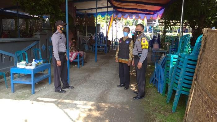Petugas menjaga lokasi pesta pernikahan yang dibubarkan karena mempelai dan orang tua positif Corona, Sragen, Minggu (30/5/2021).