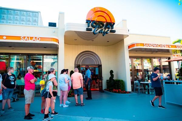 Terlihat foto-foto pengunjung yang berdiri dalam antrean, naik roller coaster, dan berjalan melalui toko suvenir.