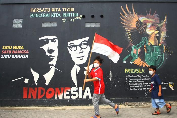Dua bocah berlari mengibarkan bendera merah putih saat perayaan hari lahir Pancasila di Kampung Tematik Kampung Teras Pancasila, Karang Tengah, Tangerang, Banten, Selasa (1/6/2021). Acara yang dilaksanakan dalam rangka memperingati hari lahirnya Pancasila bertujuan untuk memberikan wawasan dan pengetahuan tentang nilai-nilai Pancasila sejak dini. ANTARA FOTO/Muhammad Iqbal/aww.