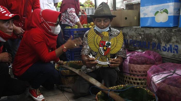 Relawan mengetes pedagang untuk menyanyikan lagu Garuda Pancasila di Pasar Gede Solo, Jawa Tengah, Selasa (1/6/2021). Aksi tersebut digelar untuk memperingati Hari Lahir Pancasila. ANTARA FOTO/Maulana Surya/aww.