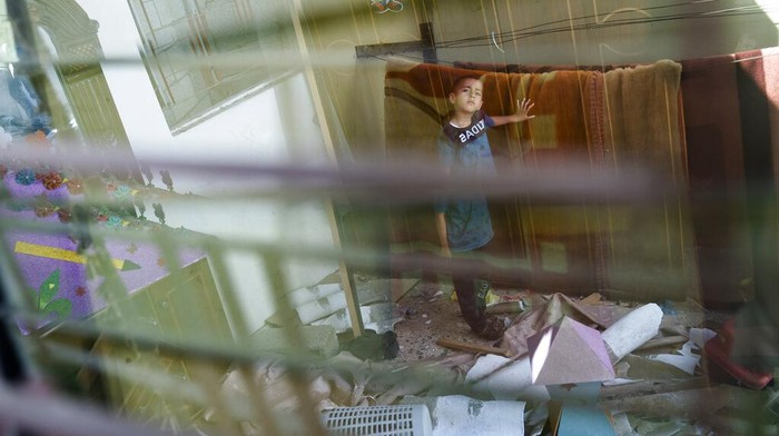 Mahmoud Al-Masri, 14, stands for a portrait in his bedroom that was damaged when an airstrike destroyed the neighboring building prior to a cease-fire that halted an 11-day war between Gaza's Hamas rulers and Israel, Wednesday, May 26, 2021, in Beit Hanoun, Gaza Strip. (AP Photo/John Minchillo)