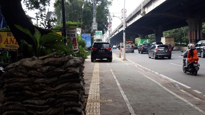 Mobil parkir di trotoar depan Halte TransJakarta Kayu Putih Rawasari