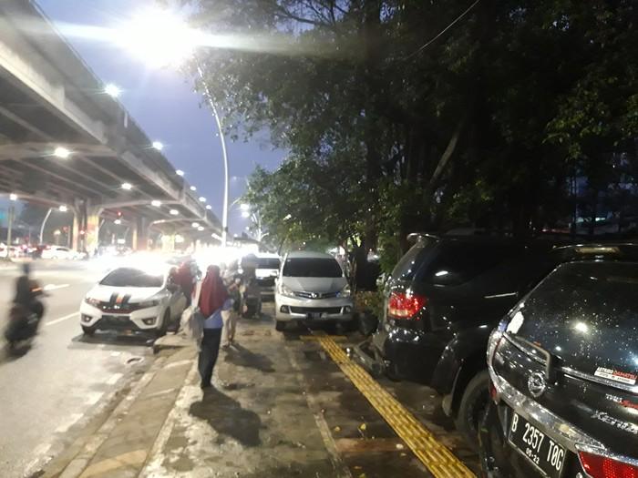 Mobil parkir di trotoar depan Halte TransJakarta Kayu Putih Rawasari, Jakarta Pusat saat malam hari.