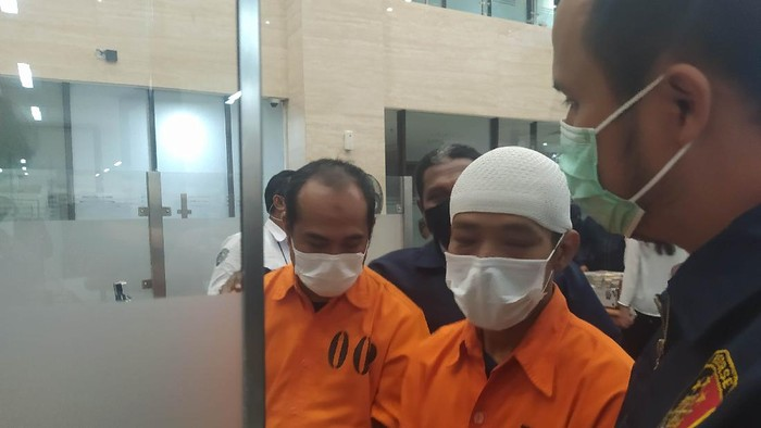 Pelaku Obligasi Dragon inisial AM mengenakan peci putih dan JM di Bareskrim Polri, Jakarta, Rabu (2/6/2021).