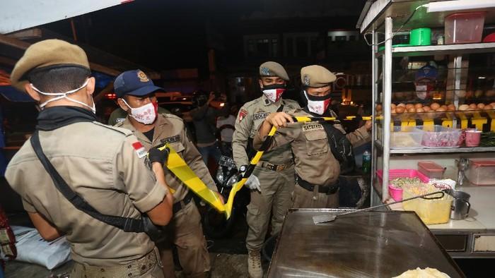 Petugas gabungan dari Satpol PP, TNI/Polri, Diskominsa dan Dinas Kesehatan menyegel salah satu warung kopi di Meulaboh, Aceh Barat, Aceh, Selasa (1/6/2021). Penyegelan warung tersebut dilakukan karena melanggar aturan protokol kesehatan COVID-19. ANTARA FOTO/Syifa Yulinnas/wsj.