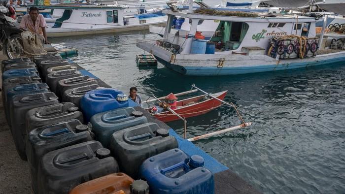 Pekerja menurunkan BBM jenis solar ke kapal nelayan di Pelabuhan Pendaratan Ikan (PPI) Donggala, Sulawesi Tengah, Selasa (1/6/2021). Pemerintah melalui  Kementerian ESDM akan mengonversi penggunaan bahan bakar minyak (BBM) ke bahan bakar gas (BBG) kepada para nelayan yang memiliki kapal penangkap ikan setara dengan 7.812 metric ton (MT). ANTARAFOTO/Basri Marzuki/rwa.