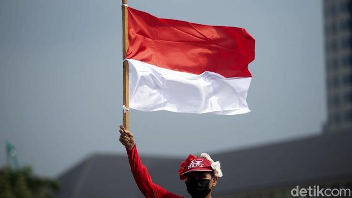Massa membentangkan bendera Merah Putih berukuran raksasa di kawasan Monas. Aksi itu dilakukan dalam rangka memperingati Hari Lahir Pancasila.