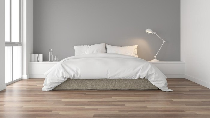 Minimal bedroom 3d render,There are wood floor and  gray wall.Furnished with brown fabric bed and white blanket .There are arch shape window nature light shining into the room.