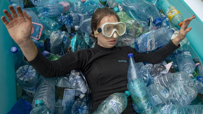 An activist lies in an inflatable pool filled with PET plastic bottles during a protest outside the environment ministry demanding the introduction of the deposit refund scheme that will stimulate the population to recycle in Bucharest, Romania, Thursday, June 3, 2021. Romania has the second lowest rate of recycling in the European Union with just 11 percent of the waste being recycled, compared to the block's average of 47 percent. (AP Photo/Alexandru Dobre)