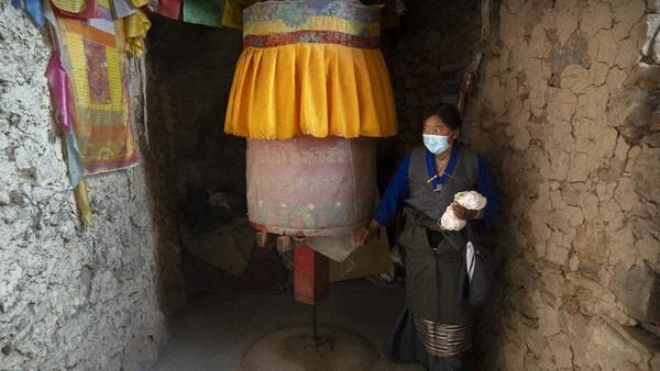 Seorang wanita Tibet memutar roda doa di sebuah kuil Buddha yang dibangun di sebuah gua di Namtso, Tibet, Rabu (2/6/2021) waktu setempat.