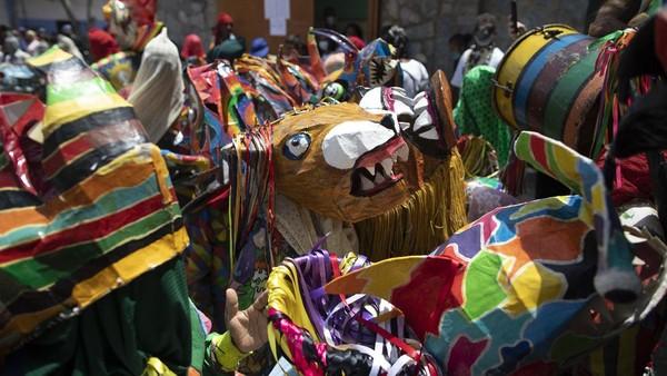Orang-orang menari dengan kostum setan untuk merayakan hari raya Katolik Corpus Christi di Naiguata, Venezuela, Kamis (3/6/2021) waktu setempat.