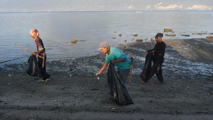 Warga memungut sampah saat aksi gotong royong membersihkan Pantai Dupa Indah di Palu, Sulawesi Tengah, Sabtu (5/6/2021). Aksi gotong royong membersihkan pantai oleh masyarakat tersebut sebagai bentuk kepedulian terhadap kelestarian lingkungan dan dalam rangka memperingati Hari Lingkungan Hidup Sedunia. ANTARA FOTO/Mohamad Hamzah/rwa.