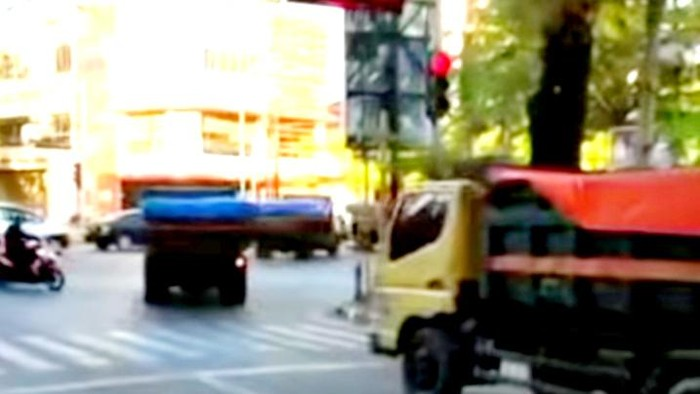 Iring-iringan truk menerobos lampu lalu lintas di Makassar.