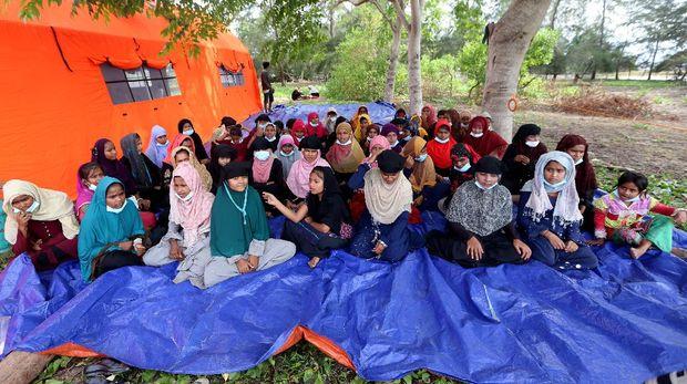 Pengungsi etnis Rohingya berada di Pulau Idaman, pesisir Pantai Kuala Simpang Ulim, Aceh Timur, Aceh, Sabtu (5/6/2021). Sebanyak 81 orang pengungsi etnis Rohingya dengan tujuan Malaysia yang terdampar di Aceh pada 4 Juni 2021 tersebut masih menunggu penanganan dari pihak terkait. ANTARA FOTO/Irwansyah Putra/rwa.