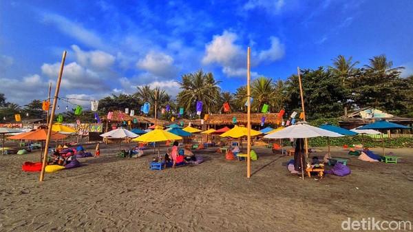 Payung-payung ala-ala Bali, kemudian Bean Bag yang nyaman untuk bersandar terlihat berjejer rapi di pesisir pantai. Area Caffe juga tidak kalah nyaman dengan ornamen kayu dan hiasan bernuansa pantai, menghadap ke lepas pantai tepat di titik sunset.