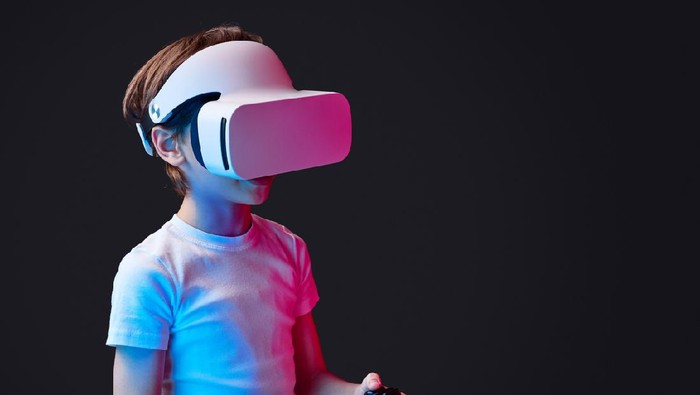 Kid wearing VR glasses and playing videogame illuminated with neon lights on black backdrop