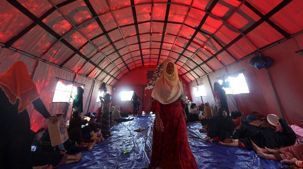 Pengungsi etnis Rohingya yang terdampar di pesisir pantai Kuala Simpang Ulim berada di sekitar tenda darurat di pulau Idaman, Aceh Timur, Aceh, Minggu (6/6/2021). Lembaga kemanusiaan yang menangani pengungsi United Nations High Commissioner for Refugees (UNHCR) masih melakukan negosiasi dengan Pemerintah setempat untuk penanganan lanjutan terhadap penempatan 81 pengungsi etnis Rohingya. ANTARA FOTO / Irwansyah Putra/foc.