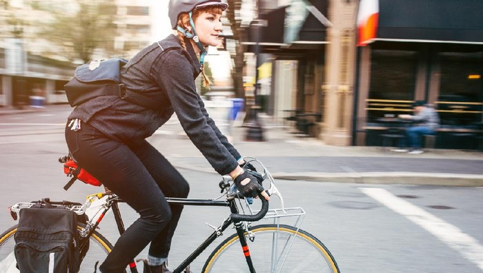 A smiling young woman commuting in an urban city environment on her street bicycle, waterproof panniers on her bike rack.  She rides the streets of downtown Portland, Oregon.  Intentional motion blur.