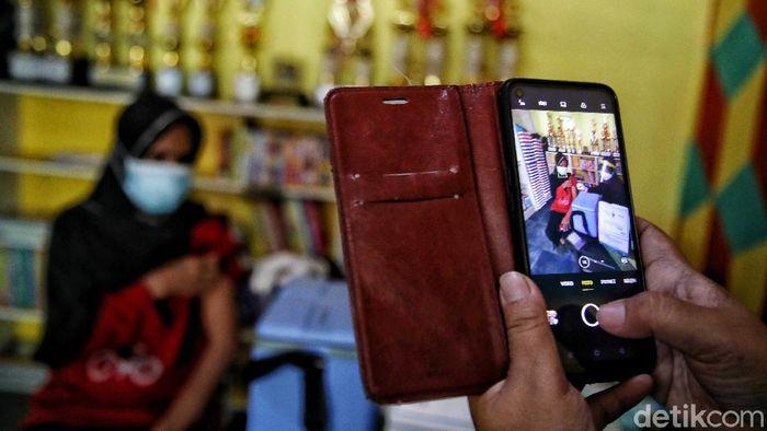 Vaksinator memberikan vaksin kepada warga di kawasan RPTRA Sindang Raya, Koja , Jakarta Utara, Senin (7/6). Vaksin tersebut diberikan kepada warga dengan rentang umur 18 - 58 tahun.