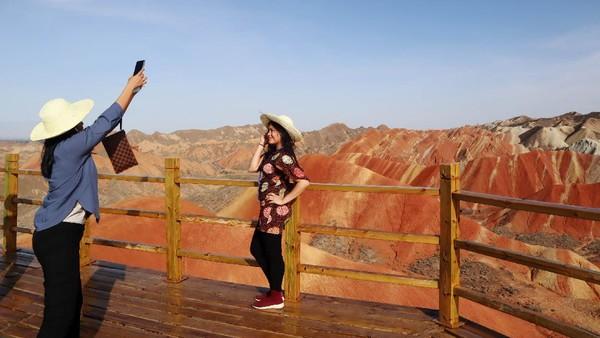 Beberapa pengunjung berfoto-foto dengan latar belakang warna-warni gunung.
