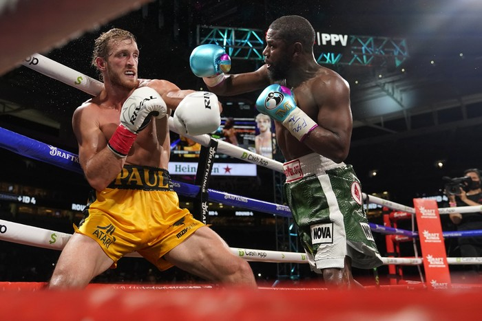 Floyd Mayweather, right, throws a punch at Logan Paul, left, during an exhibition boxing match at Hard Rock Stadium, Sunday, June 6, 2021, in Miami Gardens, Fla. (AP Photo/Lynne Sladky)