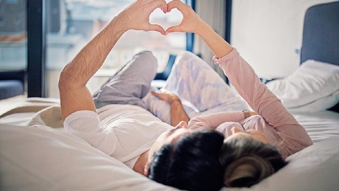 Couple is lying on the bed and making heart with their hands