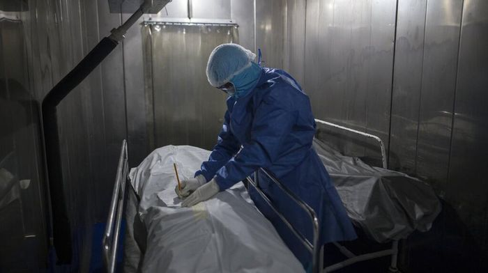 A healthcare worker tends to a COVID-19 patient in a tent set up on the soccer field of the Samaritana Hospital, in Bogota, Colombia, Thursday, June 3, 2021. Colombia has become a pandemic hotspot experiencing a third wave of COVID-19 infections and a surge in deaths. (AP Photo/Ivan Valencia)
