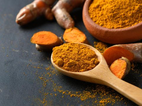 turmeric powder in wood spoon on black table, spices and herb concept