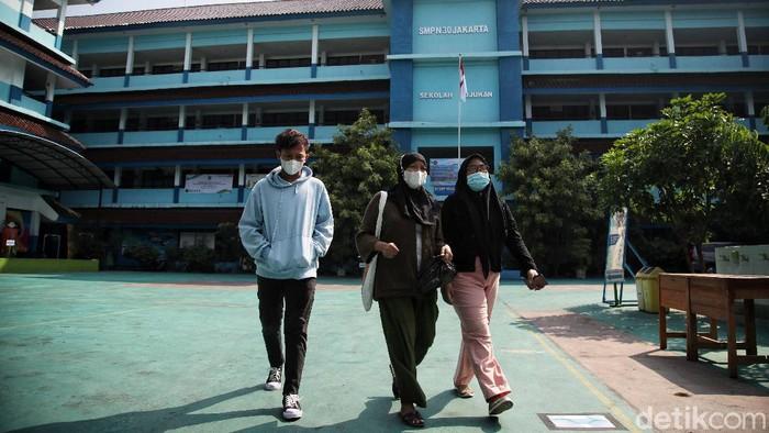 Petugas melayani wali murid kawasan Posko PPDB SMPN 30, Koja, Jakarta Utara, Senin (7/6). Pendaftaran Peserta Didik Baru (PPDB) telah dibuka pada hari ini. Kegiatan PPDB ini dilakukan secara online dari rumah.