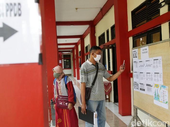 Wali murid mencari infomasi di posko Pendaftaran Penerimaan Peserta Didik Baru (PPDB) 2021 di SMA Negeri 17 Kota Bekasi, Jawa Barat, Senin (7/6/2021). Pendaftaran Penerimaan Peserta Didik Baru (PPDB) 2021 tahap 1 dibuka pada 7-11 Juni 2021. Sementara itu, untuk tahap 2 dimulai pada 25 Juni - 1 Juli 2021.