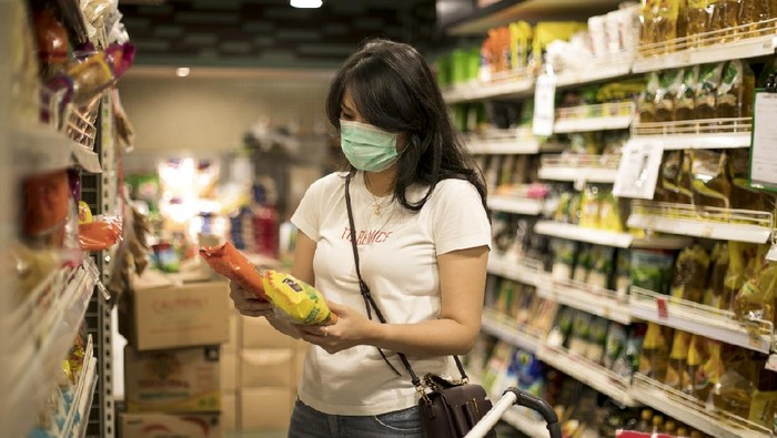 Asian young woman shopping in a grocery store and wearing protective medical mask during social distances and lockdown due to coronavirus