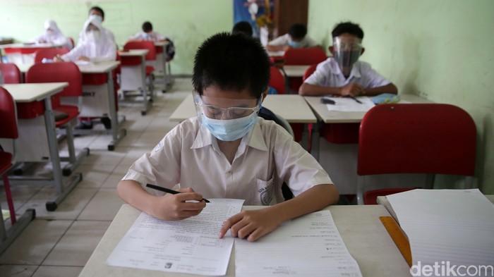Siswa-Siswi kelas 5 menjalani ujian penilaian akhir sekolah di SD Negeri Kota Baru 2 dan 3, Bekasi Barat, Kota Bekasi, Jawa Barat, Senin (7/6/2021). Ujian ini dilaksanakan secara tatap muka dengan menerapakan protokol kesehatan yang ketat dan membagi beberapa sesi kelas untuk ujian. Satu kelas terdiri dari 15 anak. Ujian ini berlangsung hingga 12 Juni 2021. Hanya kelas 4 dan 5 yang melakukan ujian tatap muka kelas lainnya laksanakan ujian secara daring.