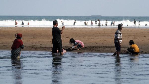 Wisatawan bermain air di kawasan Pantai Baron, Tanjungsari, Gunungkidul, DI Yogyakarta, Senin (7/6/2021).