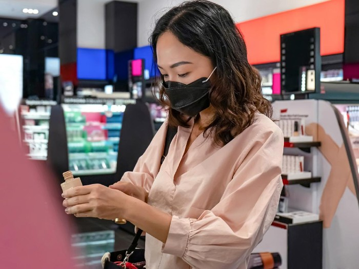 Portrait shot of a Southeast Asian woman with a face mask applying liquid foundation to her hand to match its color with her skin tone, during her make up shopping amidst Covid 19 pandemic