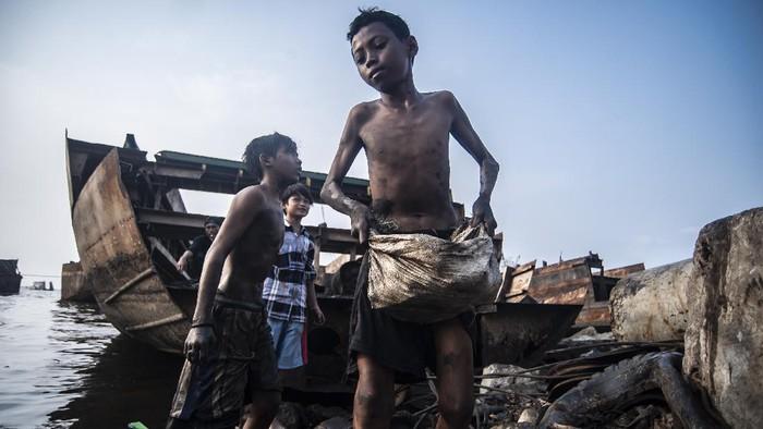 Sejumlah bocah mencari sisa besi bekas di lokasi kapal yang dibelah di Cilincing, Jakarta, Minggu (6/6/2021). Meski kegiatan mencari besi bekas dari sisa kapal yang dibelah itu berbahaya bagi anak-anak, namun mereka masih mencarinya dengan alasan untuk menambah uang jajan atau ditabung. ANTARA FOTO/Muhammad Adimaja