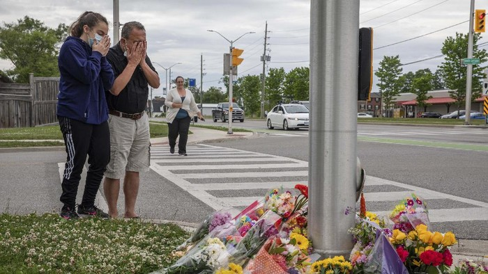 People attend a memorial at the location where a family of five was hit by a driver, in London, Ontario, Monday, June 7, 2021. Four of the members of the family died and one is in critical condition. A 20-year-old male has been charged with four counts of first degree murder and count of attempted murder in connection with the crime. (Brett Gundlock/The Canadian Press via AP)