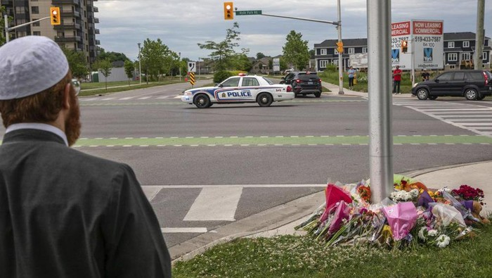 A police car passes the location where a family of five was hit by a driver, in London, Ontario, Monday, June 7, 2021. Four of the members of the family died and one is in critical condition. A 20-year-old male has been charged with four counts of first degree murder and count of attempted murder in connection with the crime. (Brett Gundlock/The Canadian Press via AP)