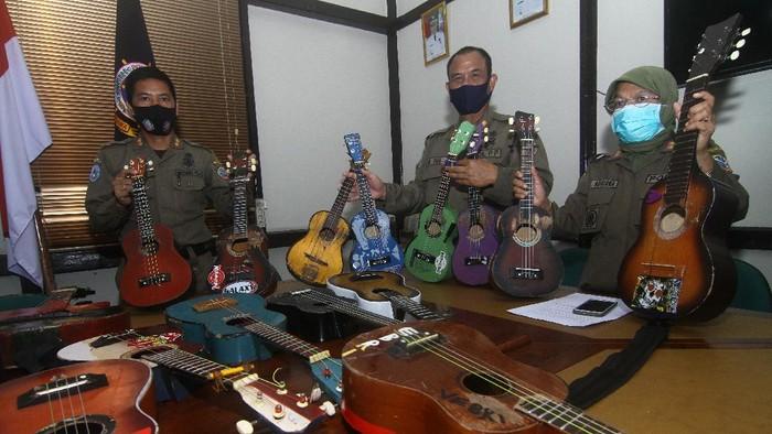Petugas Satuan Polisi Pamong Praja (Satpol PP) Kota Pontianak memperlihatkan belasan alat musik petik hasil razia pengamen saat rilis di Mako Satpol PP Kota Pontianak, Kalimantan Barat, Senin (7/6/2021). Belasan alat musik petik berupa ukulele dan gitar tersebut merupakan hasil penjaringan dari pengamen di perempatan jalan yang telah meresahkan pengguna jalan dan mengganggu ketertiban umum. ANTARA FOTO/Jessica Helena Wuysang/rwa.