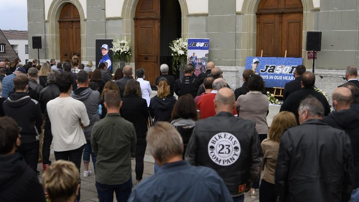 People stay next to a portrait of Jason Dupasiquer at the Church Saint-Pierre-aux-Liens during the funeral of the Swiss Moto3 rider in Bulle, Switzerland, Tuesday, June 8, 2021. Swiss motorcycle rider Jason Dupasquier died following a crash during a Moto3 qualifying for the Italian Grand Prix on Saturday, May 29, 2021 on the circuit of Mugello. (Anthony Anex/Keystone via AP)