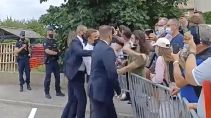 """In this grab taken from video Frances President Emmanuel Macron, centre, is slapped by a man, in green T-shirt, during a visit to Tain-l'Hermitage, in France, Tuesday, June 8, 2021. Macron denounced """"violence"""" and """"stupidity"""" after he was slapped in the face Tuesday by a man during a visit to a small town in southeastern France. The incident prompted a wide show of support for the head of state from politicians across the ideological spectrum. A video shows a man slapping Macron in the face and the presidents bodyguards pushing the aggressor away as the head of state was quickly rushed from the scene in the town of Tain-l'Hermitage. (BFM TV via AP)"""