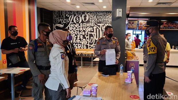 Polisi menutup dan menyegel McDonald's di Jalan Sudirman Pekanbaru, Riau imbas kerumunan pesanan menu BTS Meal (Raja Adil/detikcom)