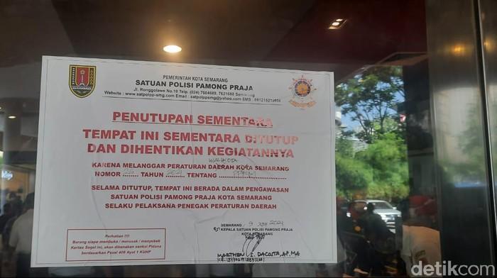 Tanda ditutup sementara McDonalds yang dipasang Satpol PP di gerai Mal Ciputra, Rabu (9/6/2021).