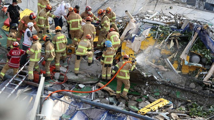Firefighters search for survivors following a collapsed building in Gwangju, South Korea, Wednesday, June 9, 2021. A building being demolished in southern South Korea collapsed on Wednesday, sending debris falling on nearby vehicles and seriously injuring several people, officials said(Chung Hoi-sung/Yonhap via AP)