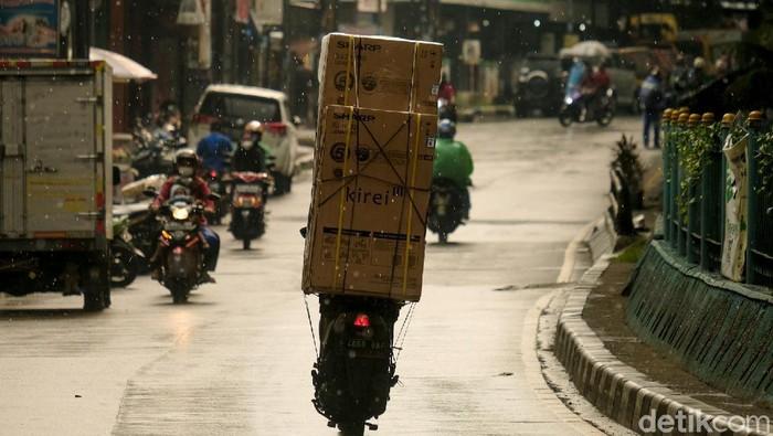 Seorang pemotor yang membawa barang berukuran besar melintasi kawasan Ciputat. Pemotor itu diketahui mengangkut kulkas. Ini potretnya.